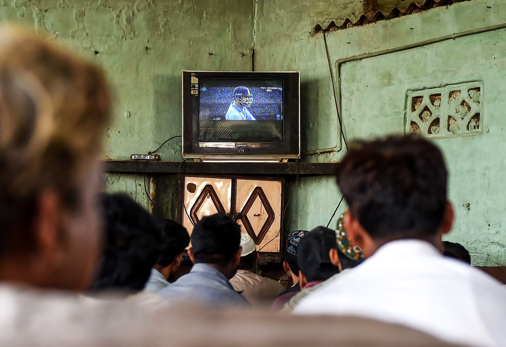 Men watch a live broadcast of the match between on a television at a small restaurant in Karachi. ─ AFP