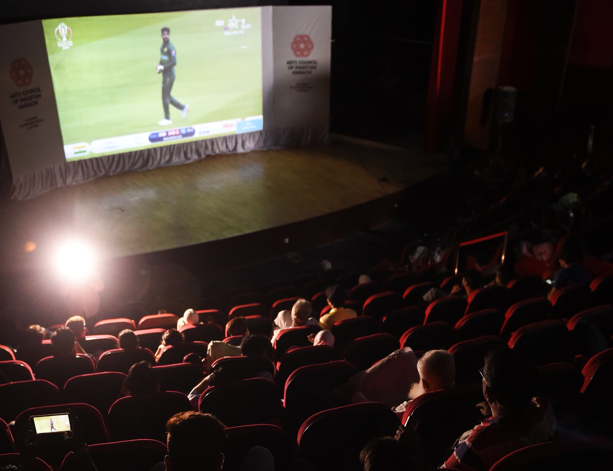 Pakistani people watch a live broadcast of the match between in a theatre in Karachi. ─ AFP