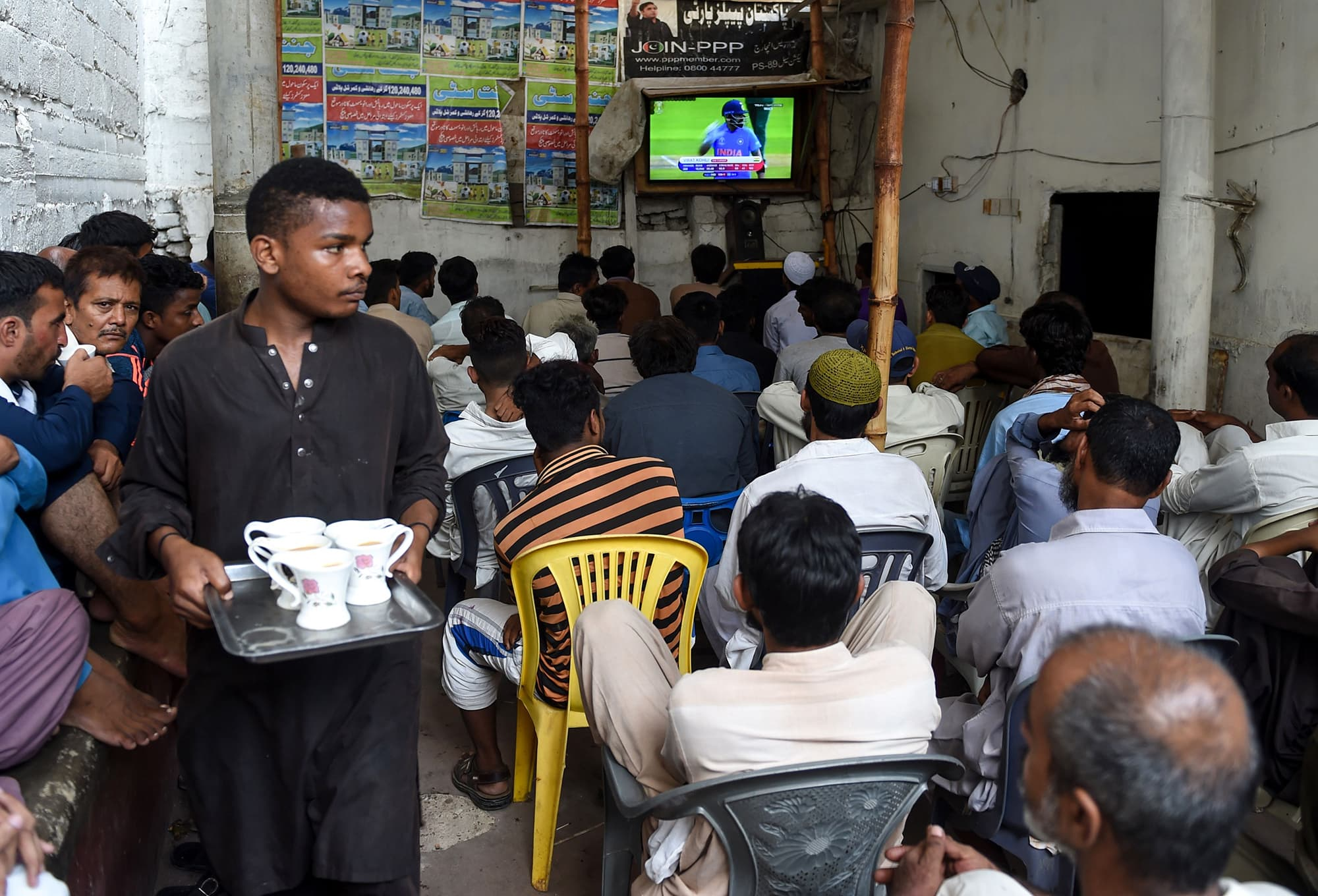 Pakistani people watch a live broadcast of the match on a television at a restaurant in Karachi. ─ AFP