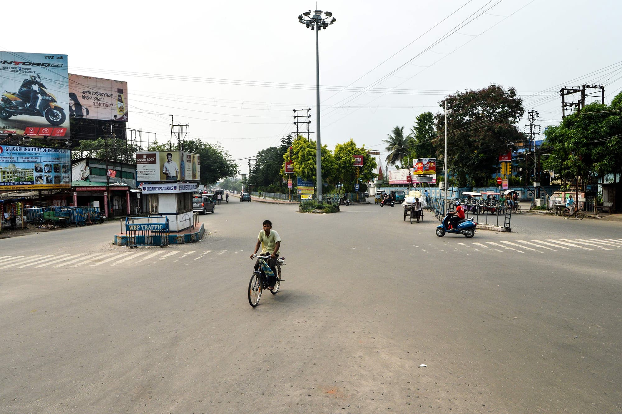 An Indian cyclist pictured on what is usually one of the busiest roads in Siliguri. The street appears deserted while the match is underway. ─ AFP