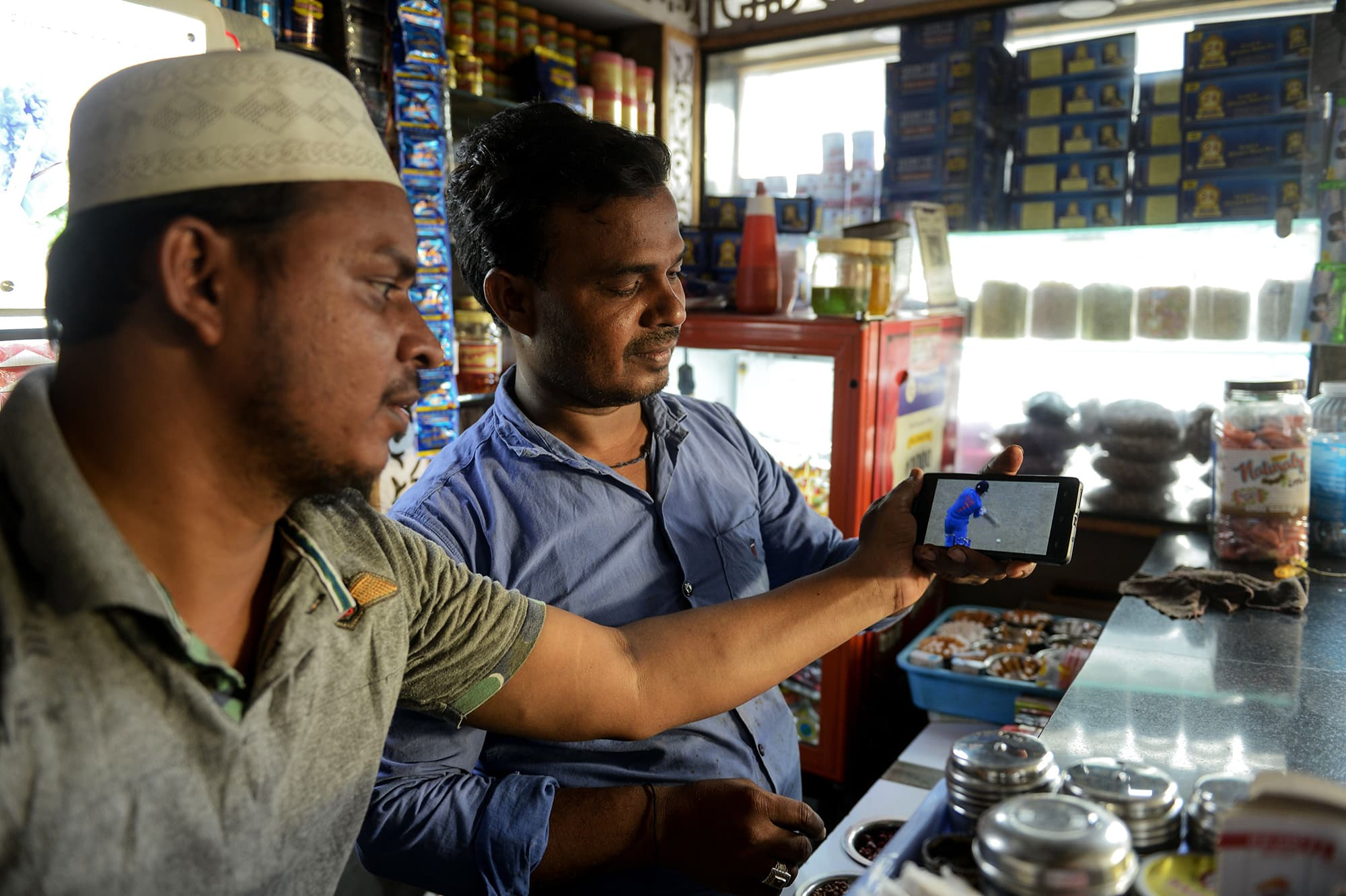 Indian fans watch a live broadcast of the match on a mobile phone at a paan shop in Hyderabad. ─ AFP