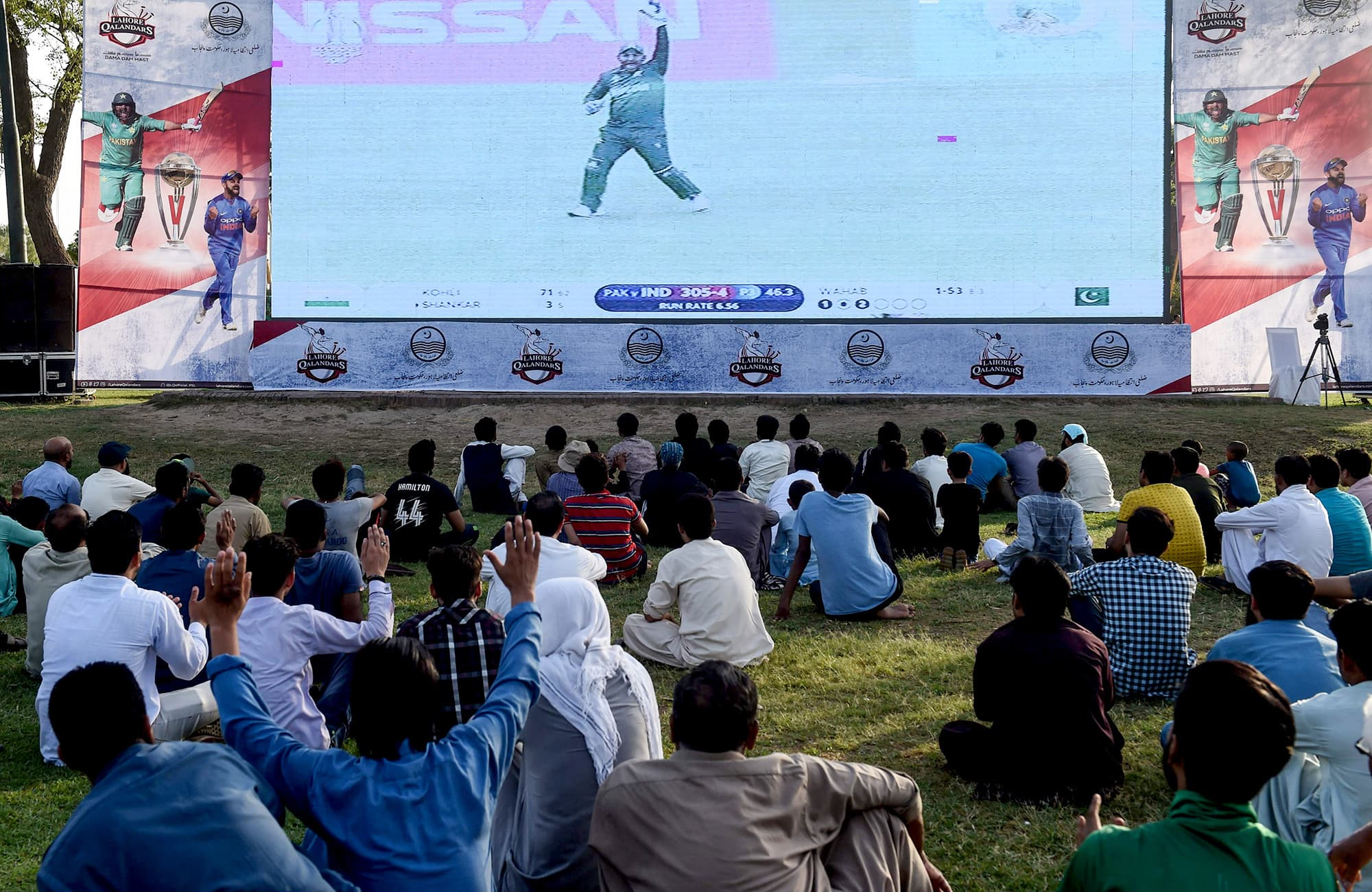 Pakistani people watch a live broadcast of the match on a big screen set up at a park in Lahore. ─ AFP