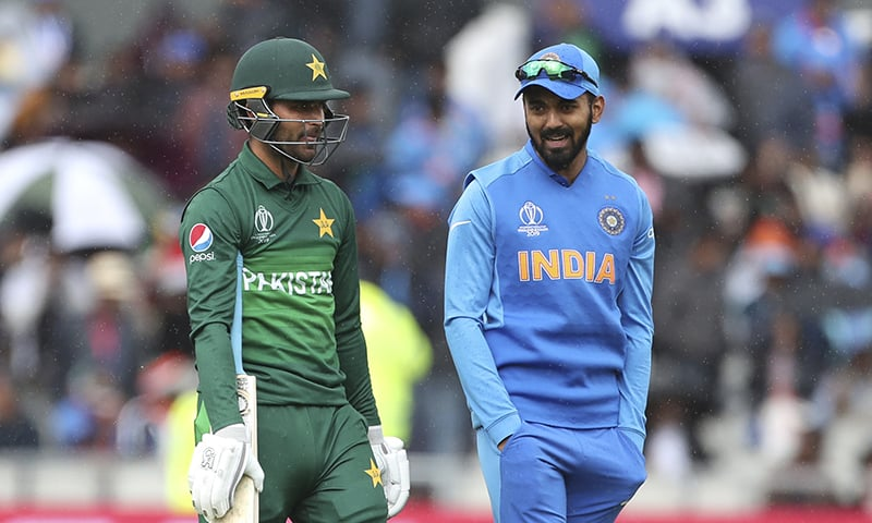 Fakhar Zaman, left, and India's KL Rahul interact as they wait for play to resume during the Cricket World Cup match between India and Pakistan. — AP