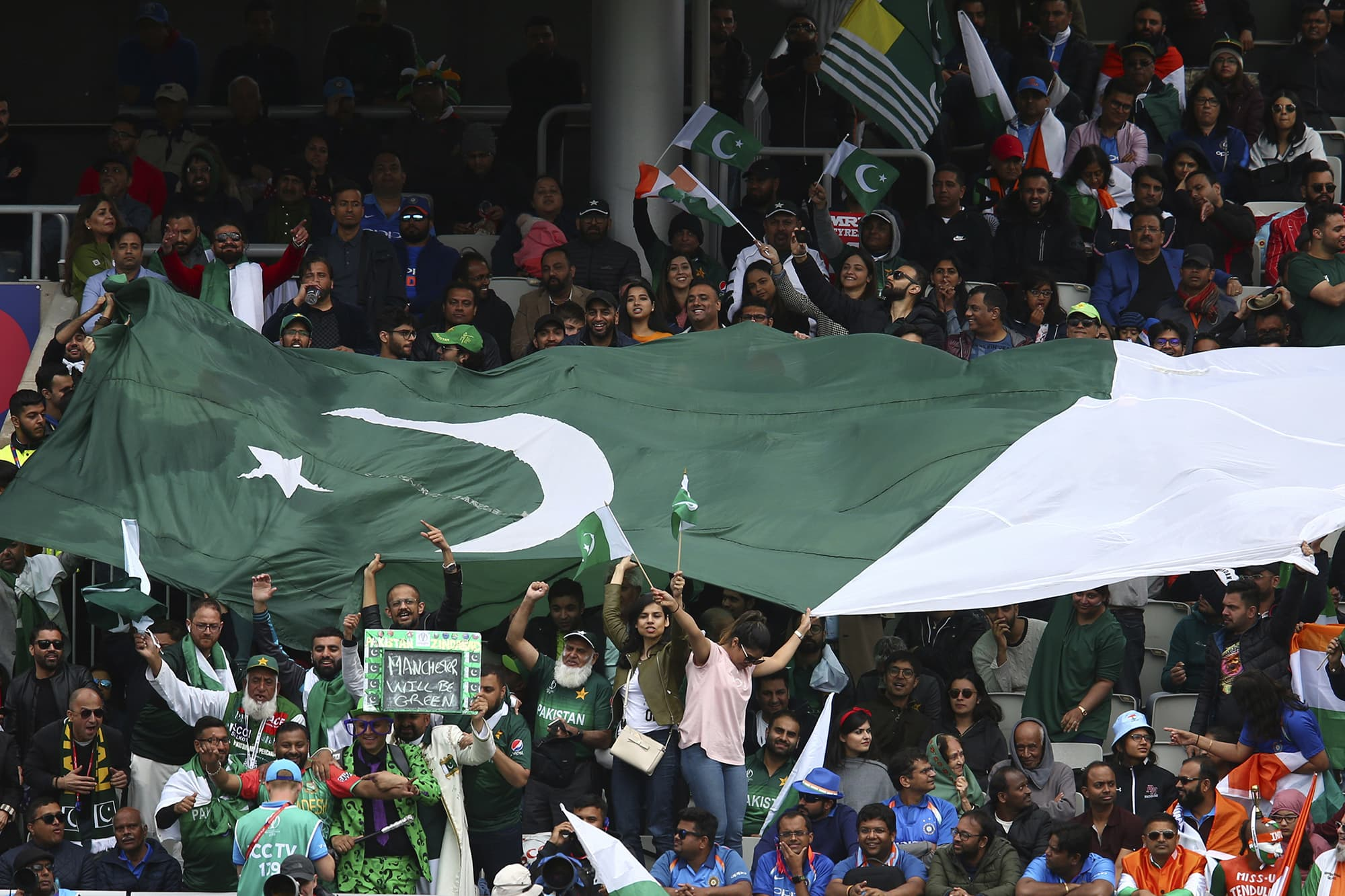 Pakistani fans holding a large flag cheer during the match. ─ AP