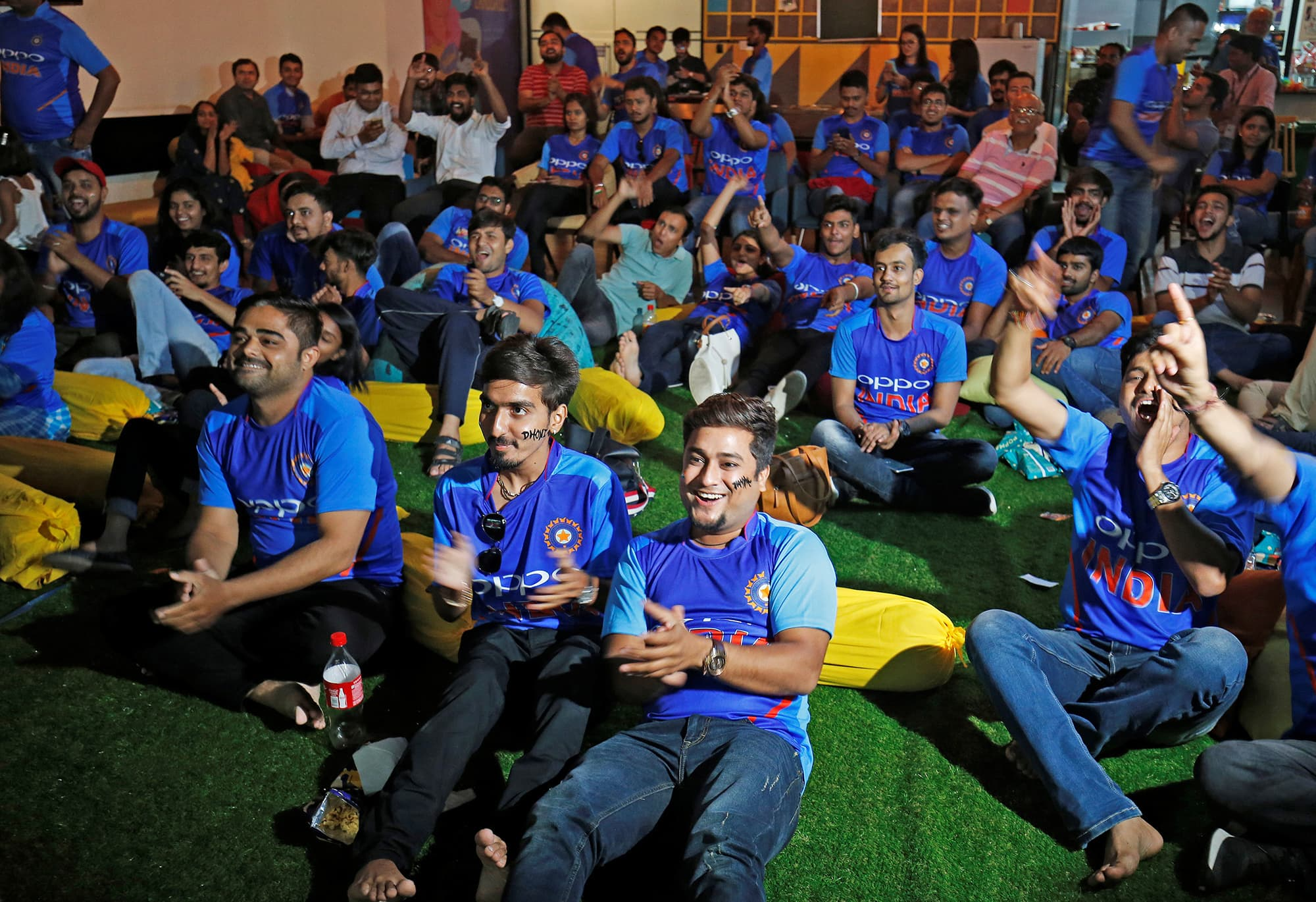 Fans react as they watch the match between India and Pakistan on a screen in Ahmedabad. ─ Reuters