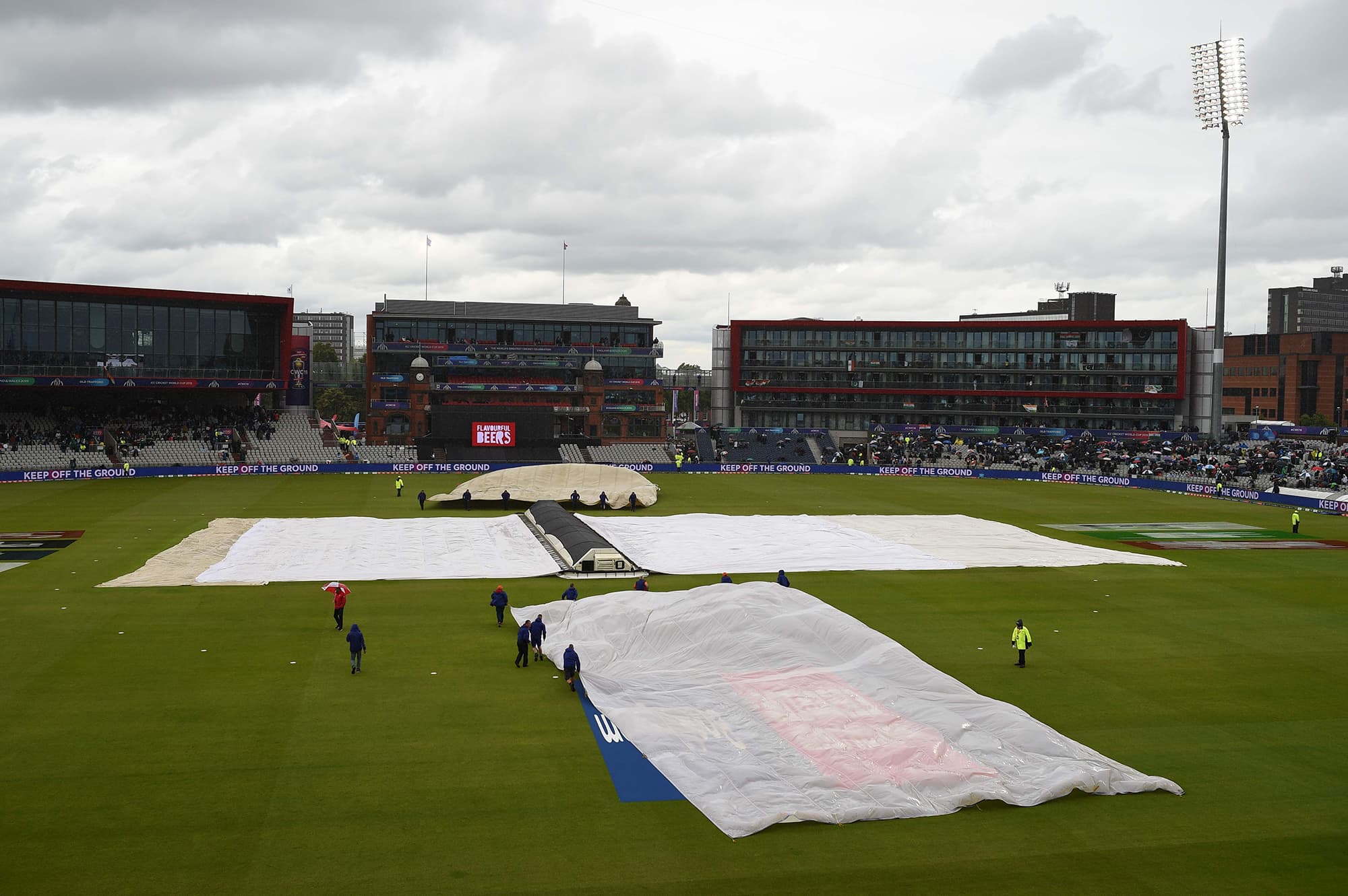 The covers and floodlights are on as rain stops play during the match between India and Pakistan at Old Trafford. — AFP