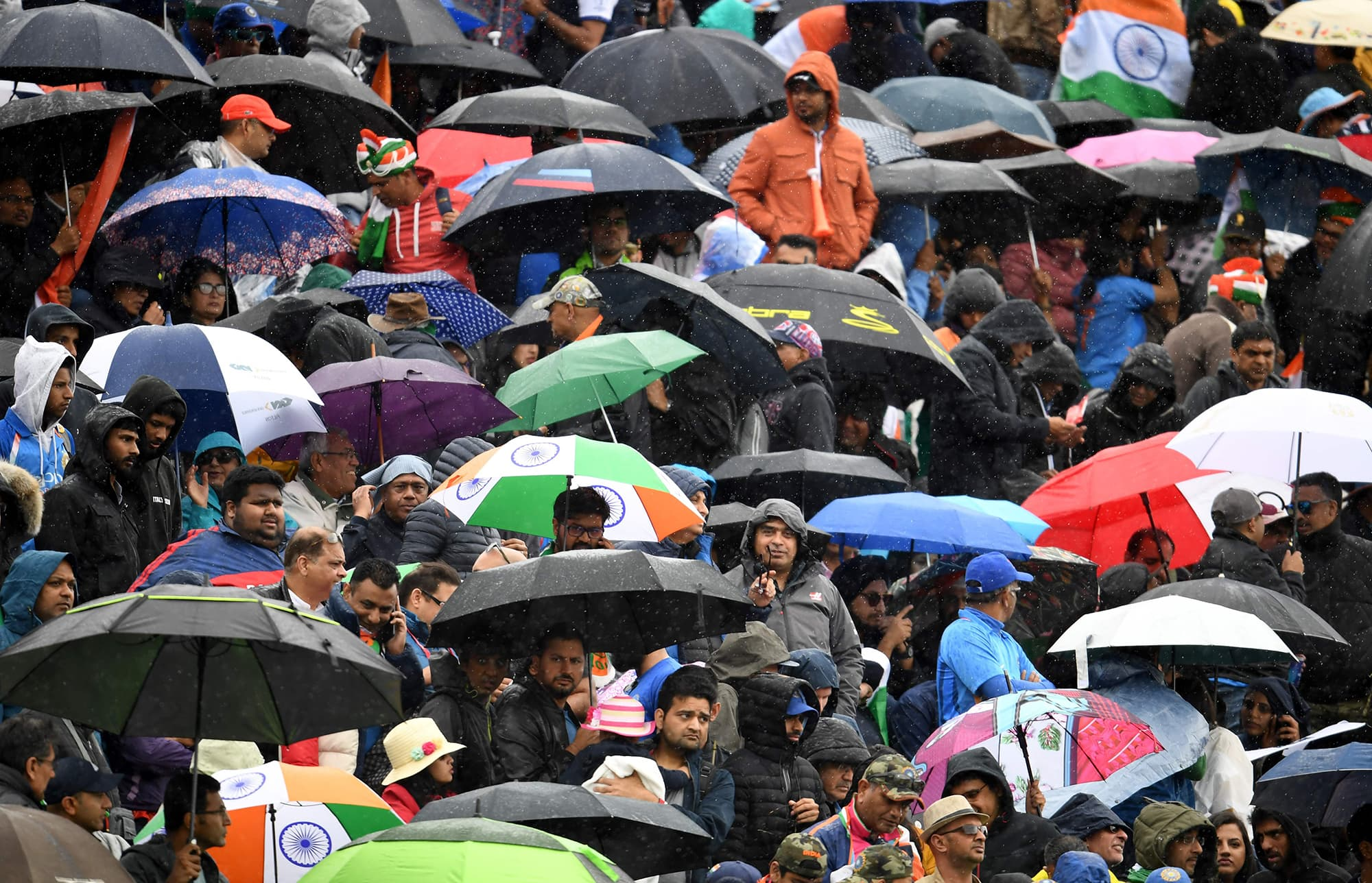 Spectators take cover under umbrellas as rain stops play. ─ AFP