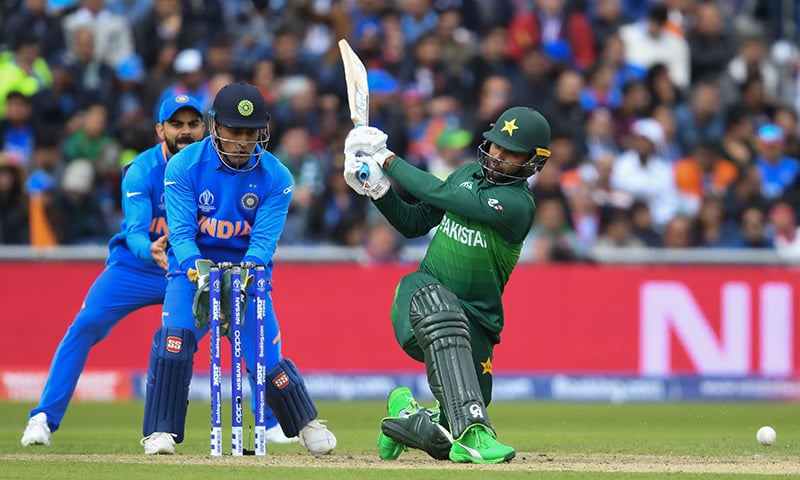 Fakhar Zaman (R) is watched by India's Mahendra Singh Dhoni (C) and India's captain Virat Kohli (L) as he plays a shot during the 2019 Cricket World Cup group stage match between India and Pakistan. — AFP