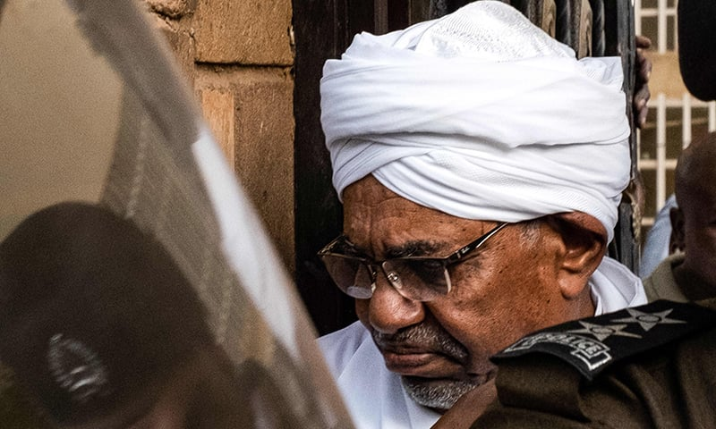 Sudan's ousted president Omar al-Bashir is escorted into a vehicle as he returns to prison following his appearance before prosecutors over charges of corruption and illegal possession of foreign currency, in the capital Khartoum on June 16. — AFP