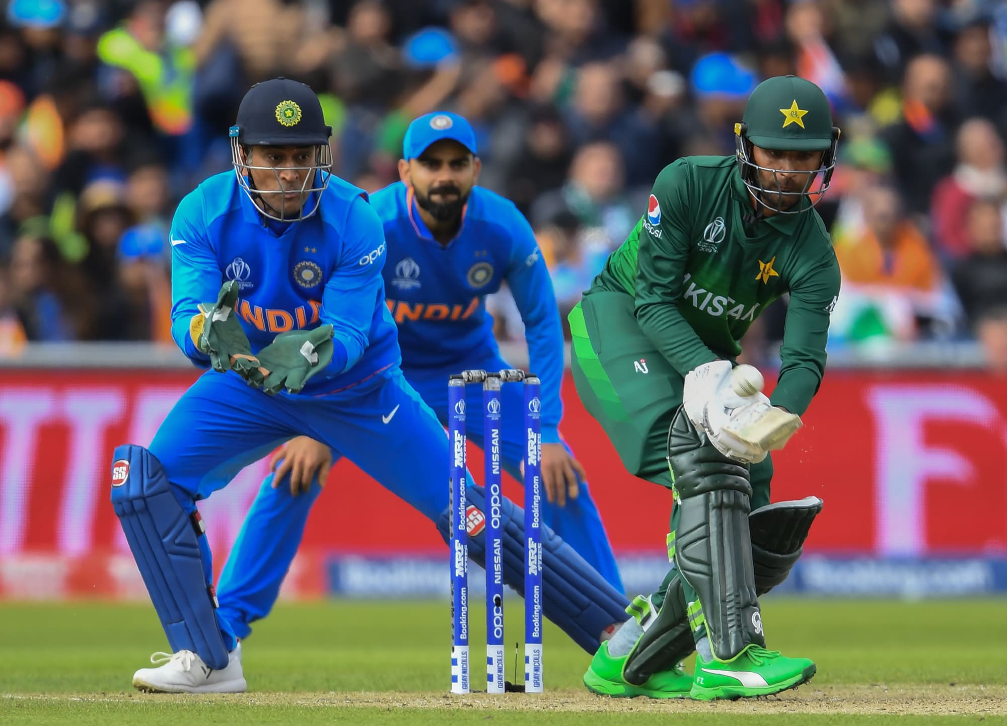 Fakhar Zaman is watched by MS Dhoni (L) Virat Kohli (C) as he plays a shot. ─ AFP