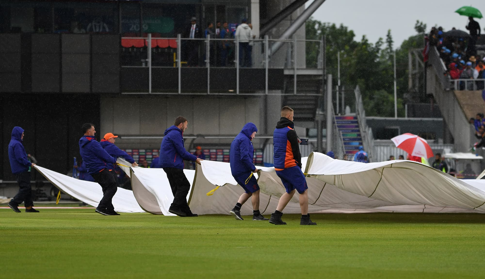 Ground staff cover the playing area as rain stops play during the 2019 Cricket World Cup group stage match between India and Pakistan at Old Trafford in Manchester. ─ AFP