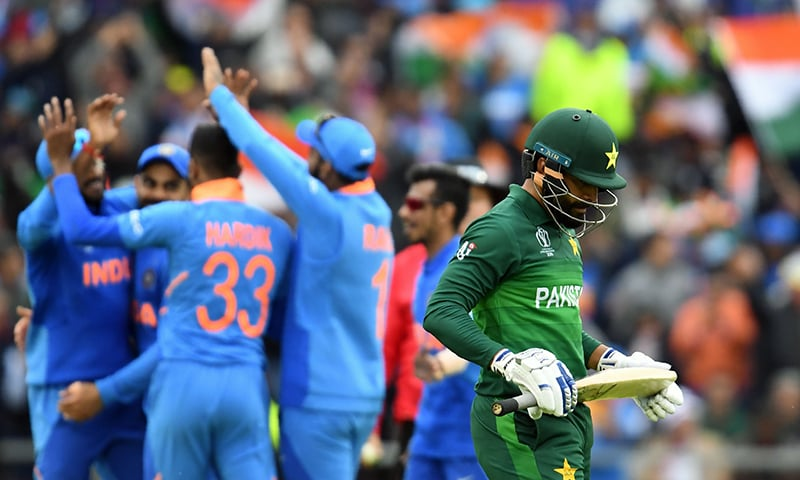 Pakistan's Mohammad Hafeez (R) walks back to the pavilion after his dismissal during the 2019 Cricket World Cup group stage match between India and Pakistan. — AFP