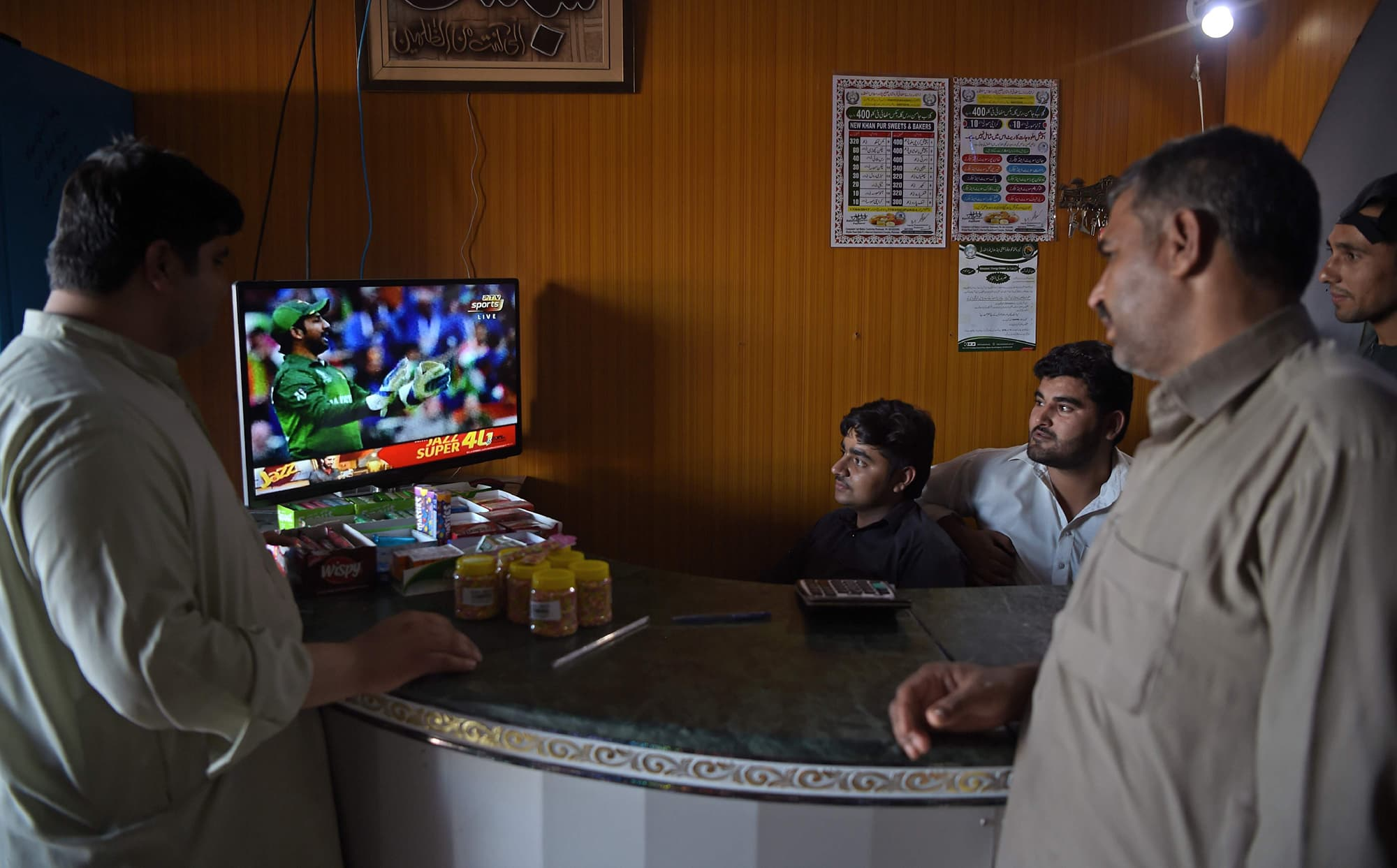 Pakistanis watch the match on a television screen in Peshawar. ─ AFP