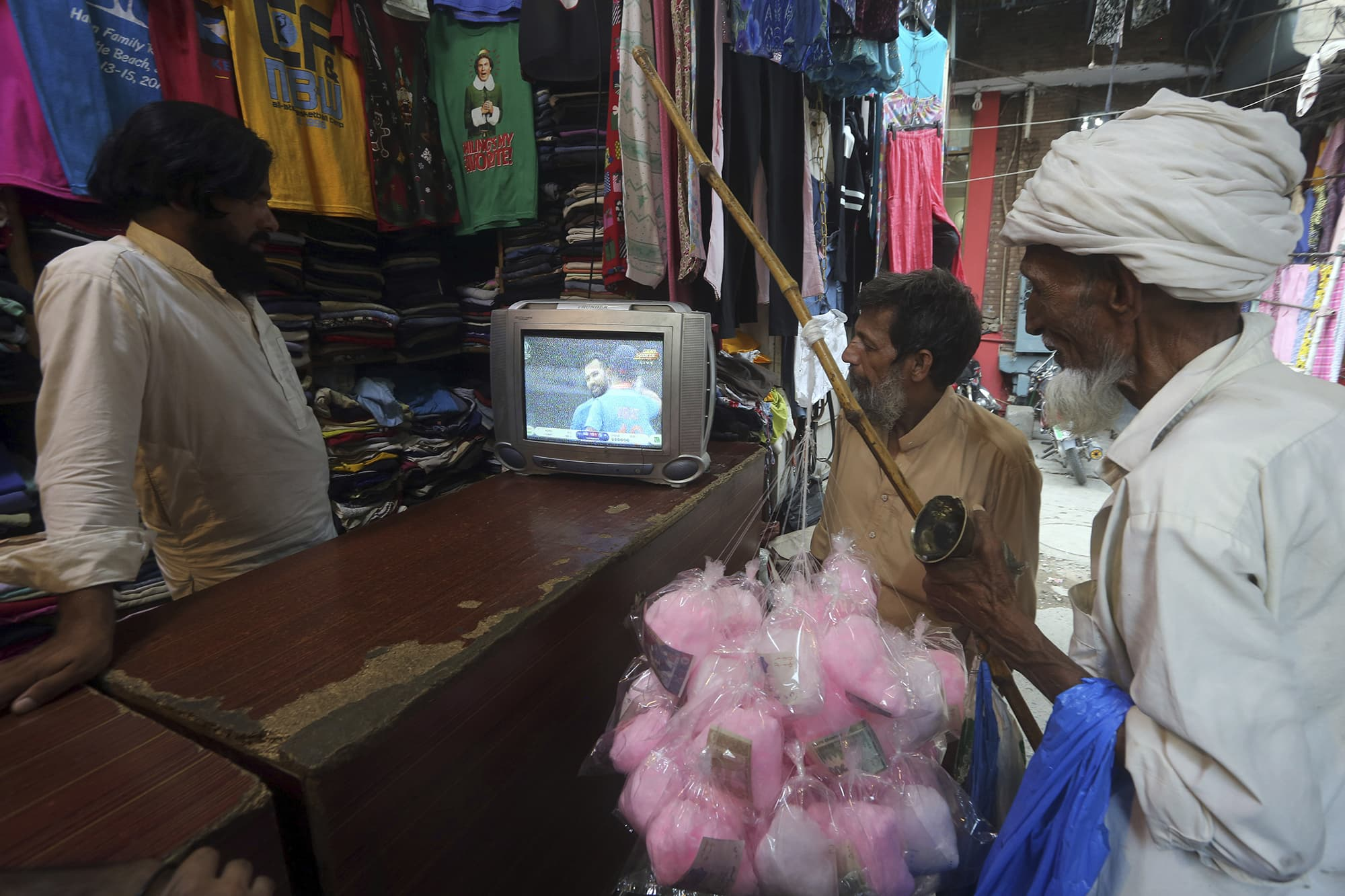 A shopkeeper and passersby watch the match at a shop in Lahore. ─ AP