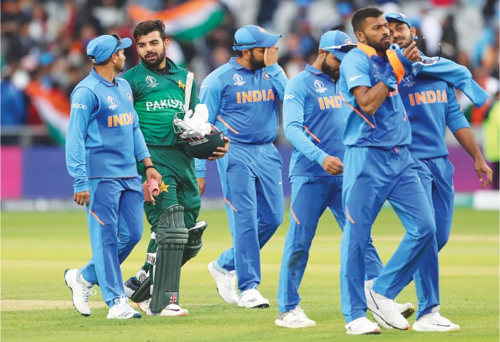 MANCHESTER: Shadab Khan (second left) leaves the field with Indian players after the end of the World Cup match on Sunday.—AP