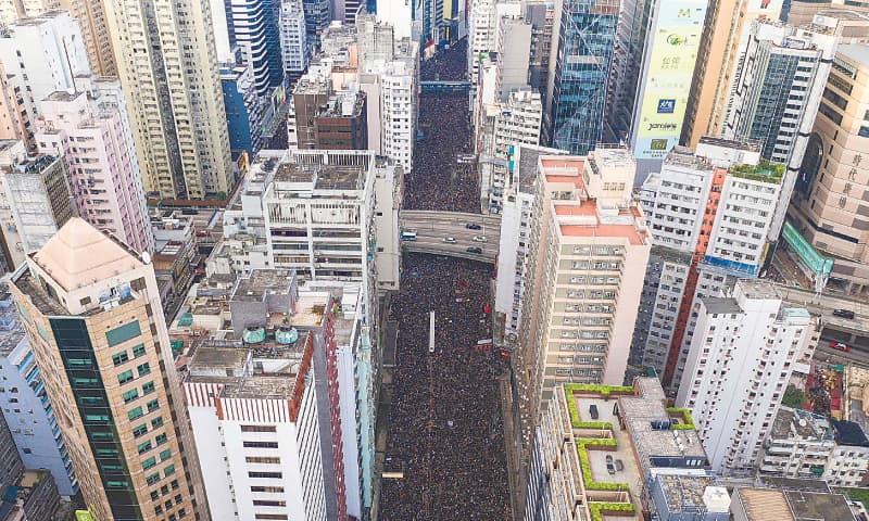 Hong Kong: This overhead view shows thousands of protesters marching through a street to protest the extradition law proposal. — AFP