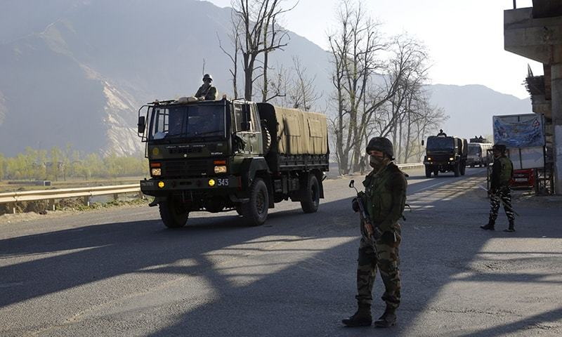 An Indian army soldier stands guard as an army convoy moves on a highway on the outskirts of Srinagar. ─ AP/File