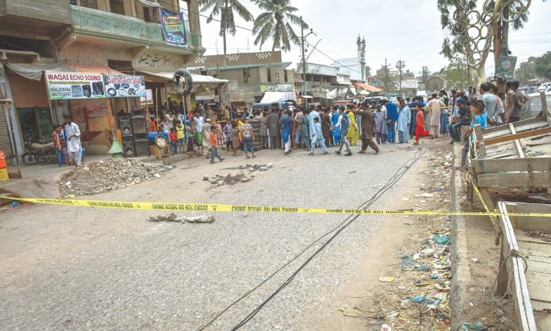A CROWD gathers at the crime scene in Orangi on Monday.—Fahim Siddiqi / White Star