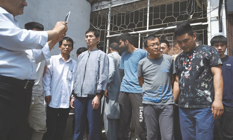 File photo of detained Chinese nationals outside a court in Islamabad.—AP