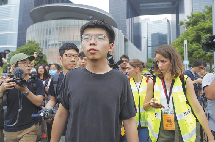 HONG KONG: Reporters try to get close to pro-democracy activist Joshua Wong (centre) after he spoke to protesters near the legislative council building on Monday. — AP