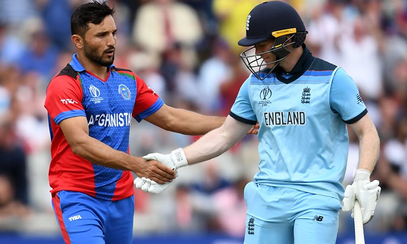 England's captain Eoin Morgan (R) is congratulated by Afghanistan's captain Gulbadin Naib after he lost his wicket for 148 runs. — AFP