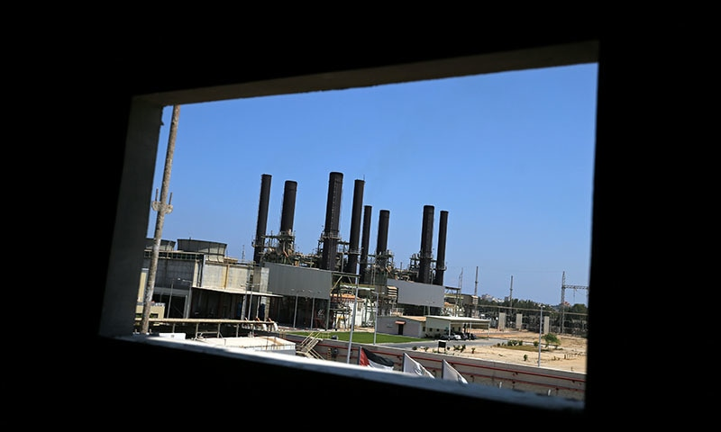 The Gaza power plant is seen through a building window, in the central Gaza Strip on June 18. — Reuters