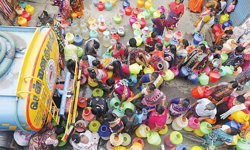 Chennai: People stand in queues to fill vessels with drinking water from a tanker. — AP