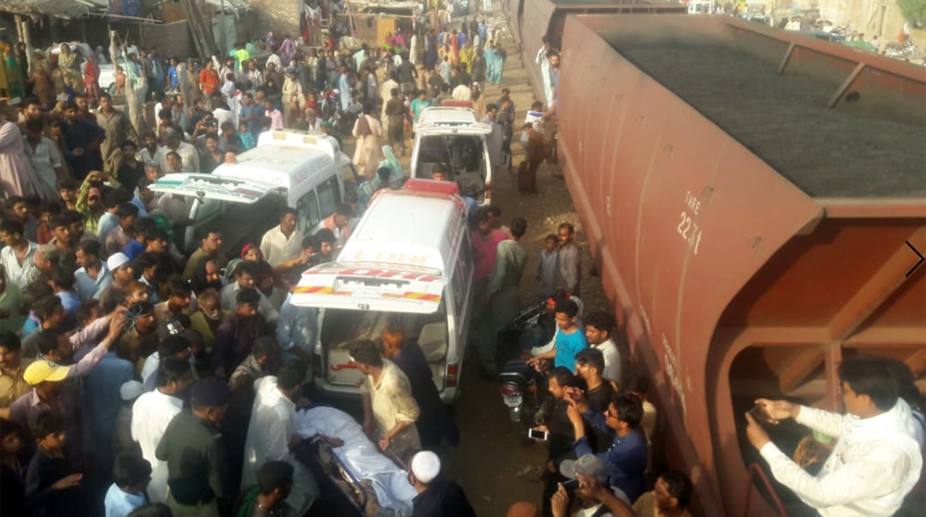 Edhi volunteers wade through large crowds to carry the bodies over to the ambulance. — Photo by Mohammad Hussain Khan