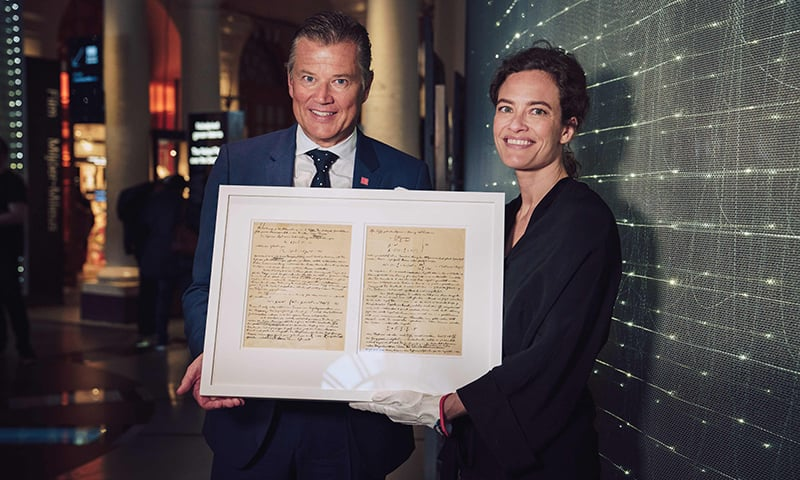 A handout picture released by the Nobel Prize Museum on June 19 shows Swedish businessman Per Taube (L), posing next to the director of the Nobel Prize Museum Erika Lanner, with the handwritten two-page document by Albert Einstein that he donated to the Museum. — AFP