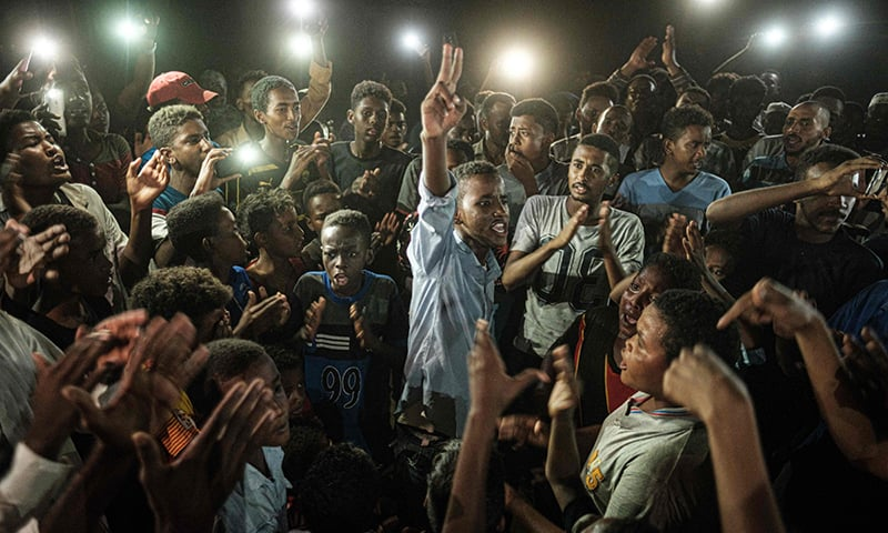 People chant slogans as a young man (unseen) recites a poem, illuminated by mobile phones, before the opposition's direct dialog with people in Khartoum on June 19. — AFP