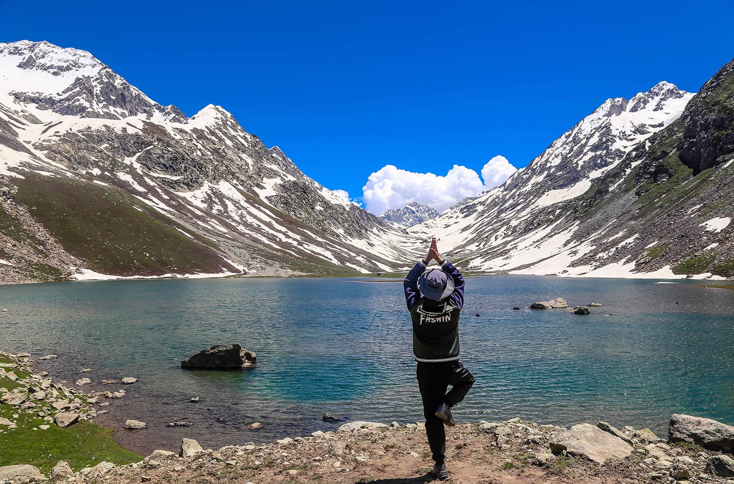 A trekker poses for photo in front of Izmis lake. ─ Photo by author