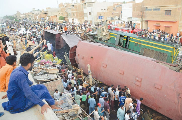 HYDERABAD: Crowds mill around the place where a passenger train slammed into a goods train on Thursday. Three people were killed in the collision.—Umair Ali