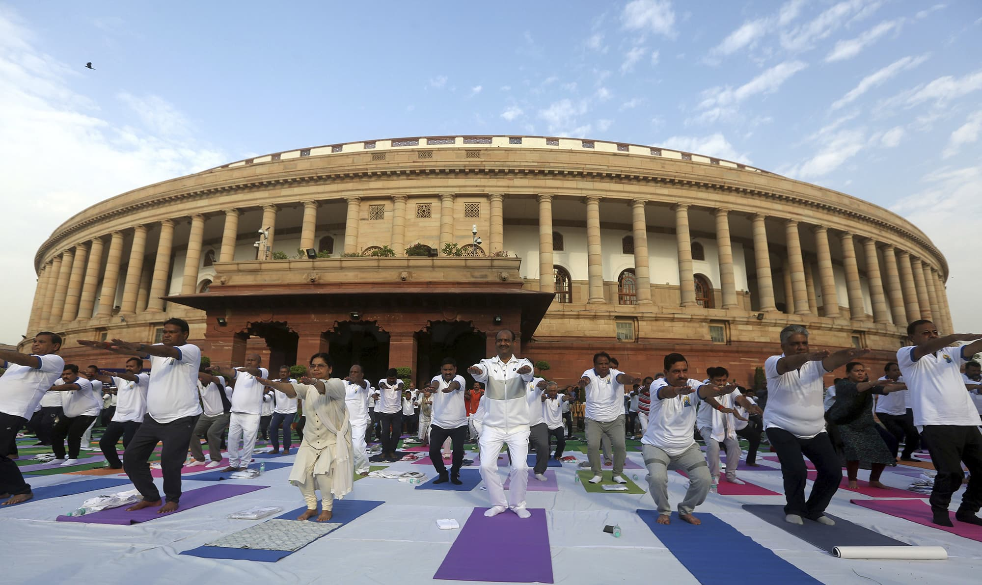 Indian lawmakers perform yoga in front of the parliament house to mark International Yoga Day in New Delhi, India on June 21. — AP