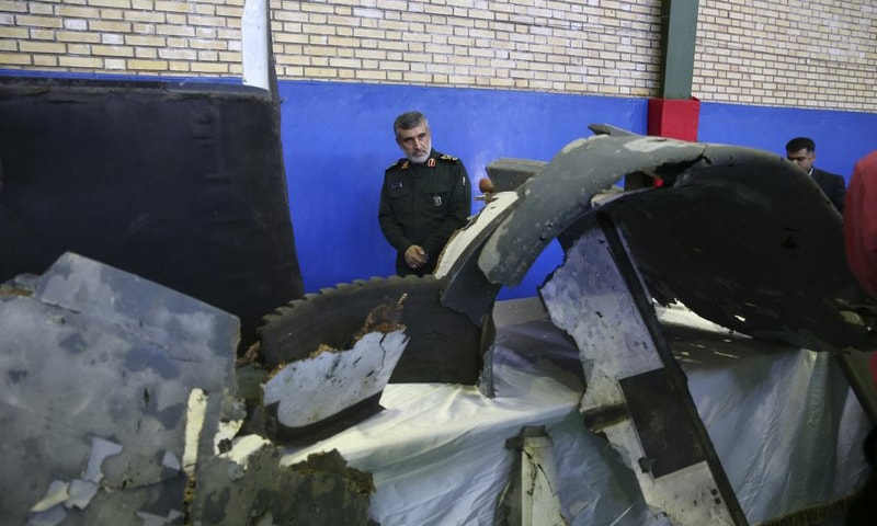 Head of the Revolutionary Guard's aerospace division Gen. Amir Ali Hajizadeh on Friday looks at debris from what the division describes as the US drone that was shot down. — AP
