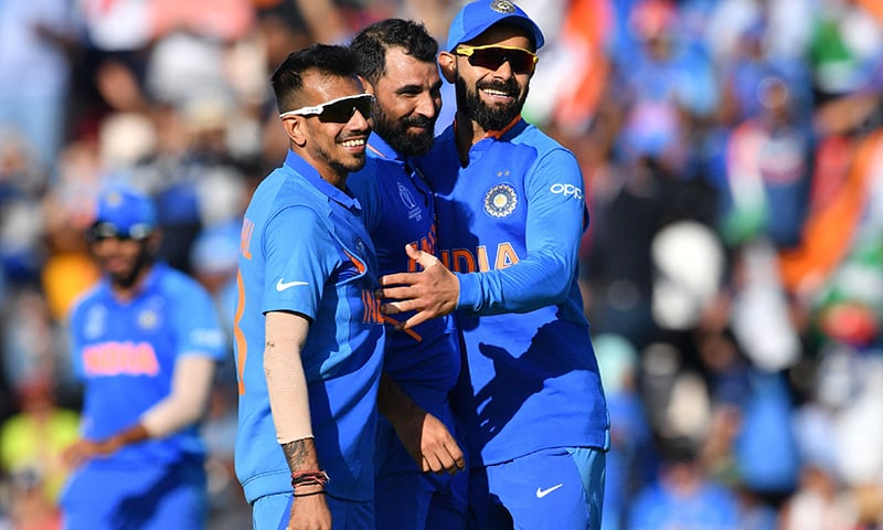 India's captain Virat Kohli (R) celebrates with teammates Mohammed Shami (C) and Yuzvendra Chahal (L) after the dismissal of Afghanistan's Mohammad Nabi. — AFP