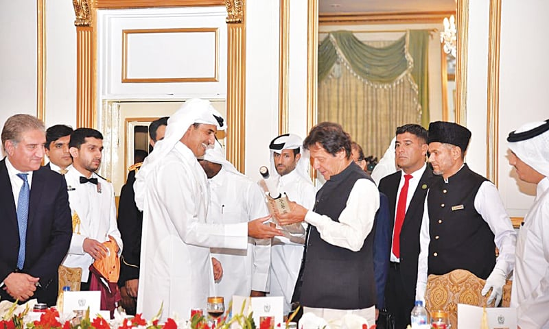 Prime Minister Imran Khan signs a cricket bat before presenting it to Qatar Emir Sheikh Tamim bin Hamad Al Thani who earlier presented him Qatar's national football team jersey on Saturday evening.
