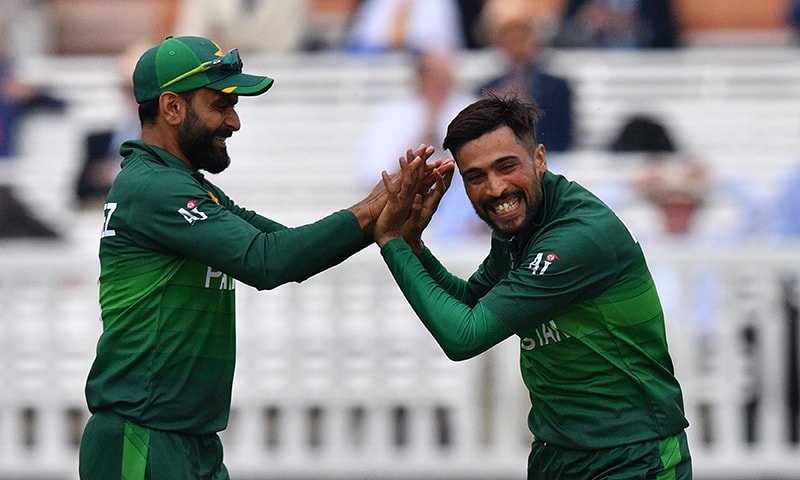 Mohammad Amir (R) celebrates with Mohammad Hafeez after the dismissal of South Africa's captain Faf du Plessis. — AFP