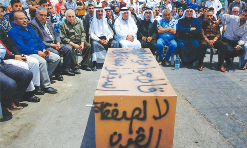 "Hebron: Palestinian men sit around a makeshift coffin with the words,  ""No to the deal of the century"", during a protest on Monday against a US-led meeting in Bahrain.—AFP"