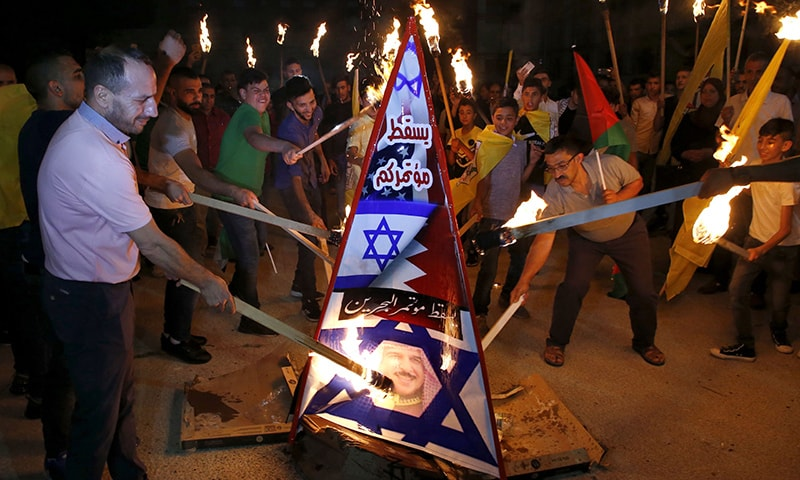 Palestinians burn a structure displaying the Israeli flag and a portrait of King Hamad al-Khalifa of Bahrain during protests against a US-led meeting this week in the Gulf kingdom on the Palestinian-Israeli conflict, in the West Bank city of Hebron on June 24. — AFP