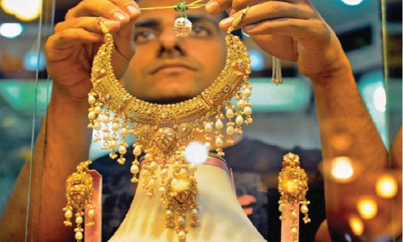 A JEWELLER is showing an necklace to customer at his shop in this file photo.