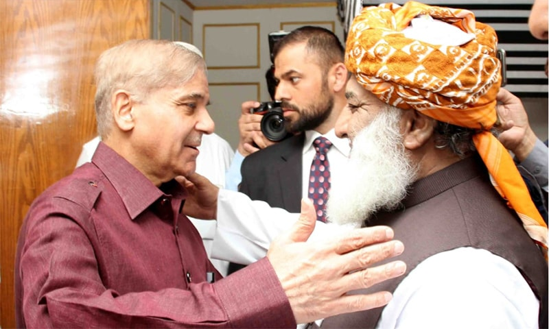 Opposition leader Shahbaz Sharif is greeted by MPC host Maulana Fazlur Rehman. — Photo by author