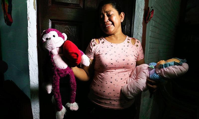 مرنے والے شخص کی والدہ اور بچی کی دادی حادثے کے بعد صحافیوں کو پوتی کے کھلونے دکھاتے ہوئے—فوٹو: اے پی