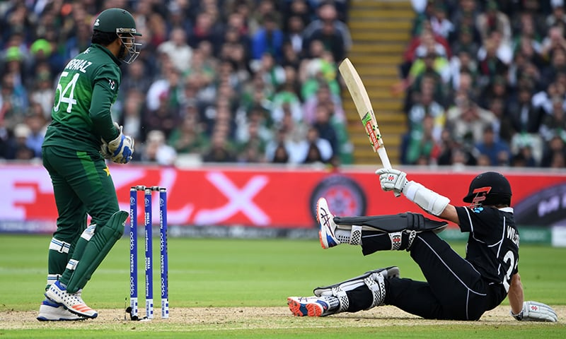 New Zealand skipper captain Kane Williamson (R) is watched by Pakistan's captain Sarfaraz Ahmed as he falls to the wicket during the 2019 Cricket World Cup group stage match between New Zealand and Pakistan at Edgbaston on June 26. — AFP