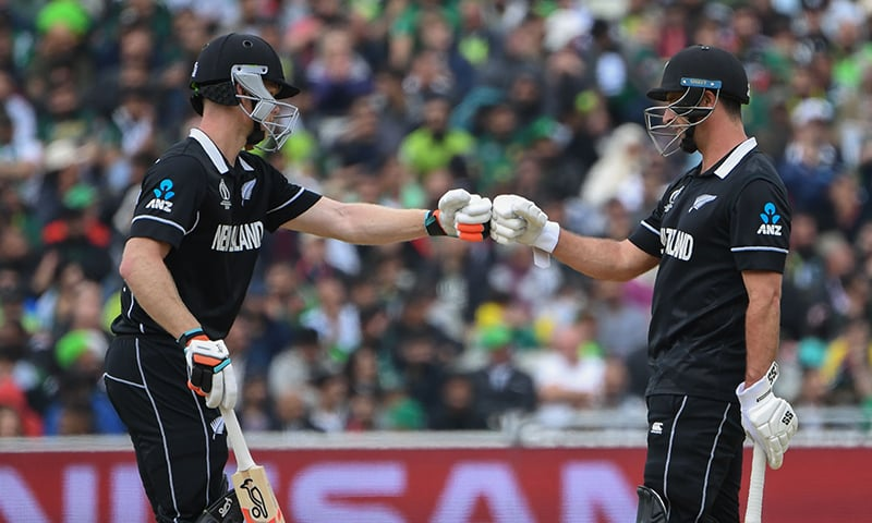 New Zealand's James Neesham (L) and teammate Colin de Grandhomme touch gloves after a boundary during the 2019 Cricket World Cup group stage match between New Zealand and Pakistan at Edgbaston on June 26. — AFP