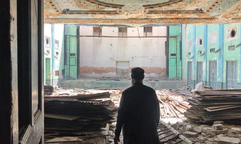 A man stands amid the rubble in the main hall of the erstwhile Capital Cinema. — Dawn
