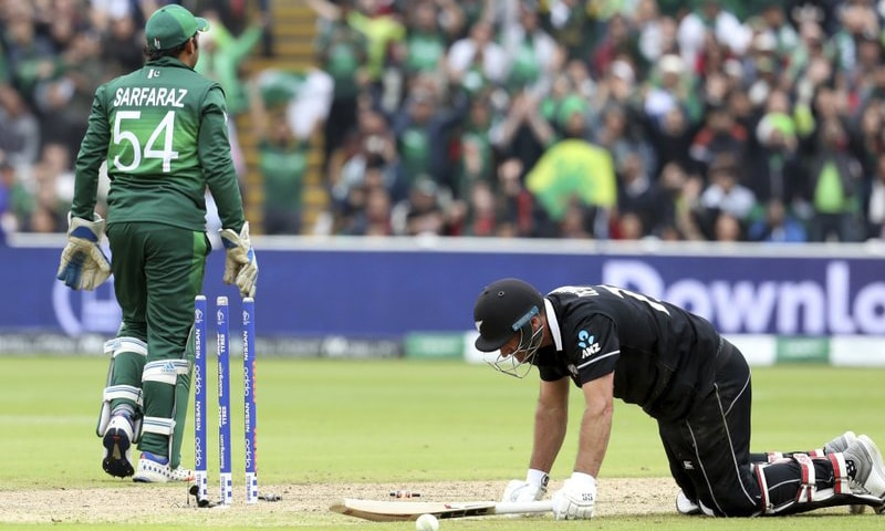 New Zealand's batsman Colin de Grandhomme, right, is run out as Pakistan's captain Sarfaraz Ahmed walks away during the Cricket World Cup match between New Zealand and Pakistan at the Edgbaston Stadium in Birmingham on June 26. — AP