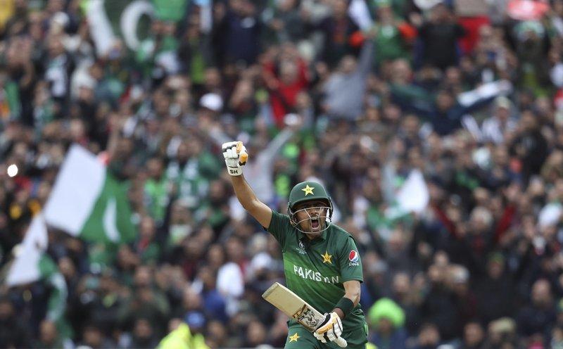 Babar Azam raises his fist to celebrate scoring a century. ─ AP