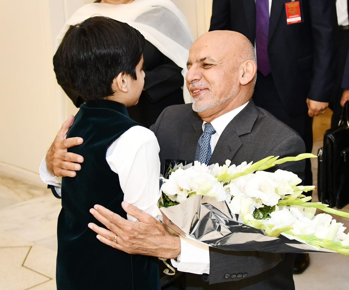 Afghan President Ashraf Ghani hugs a child as he receives a bouquet of flowers at the President House. — GOP Twitter