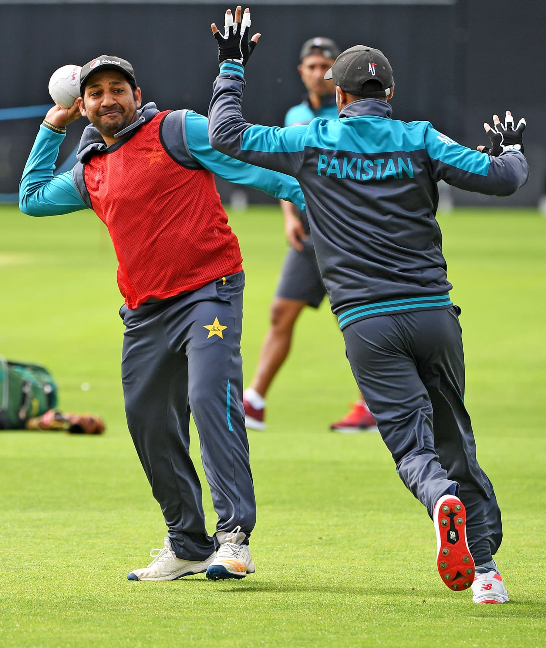Sarfaraz moves back to throw the ball during the team training session at Headingly. — AFP