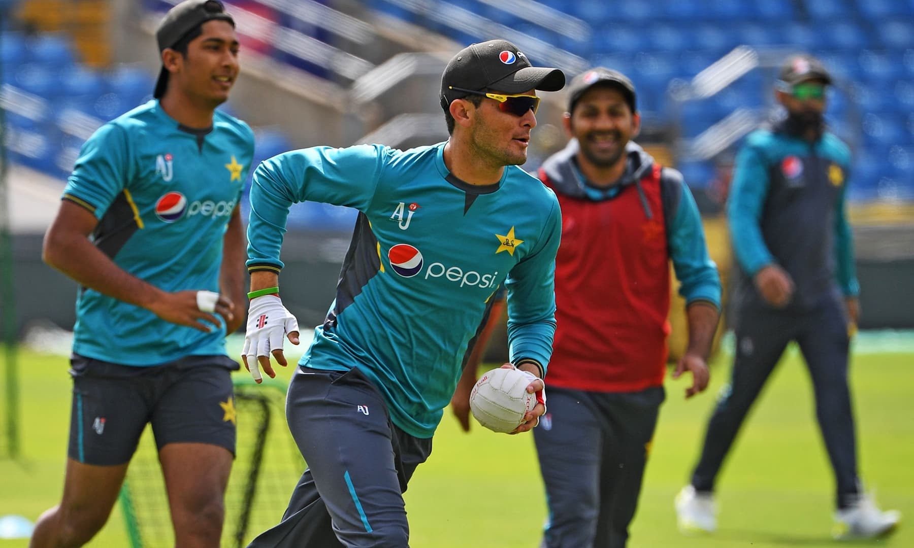 Shaheen Shah Afridi runs with the ball as skipper Sarfaraz looks on. — AFP